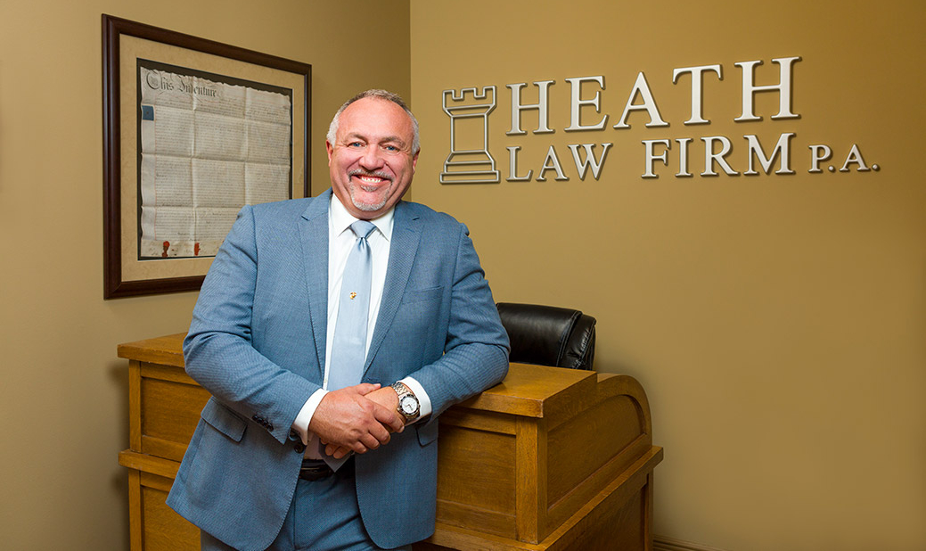 Image of James Heath in front of Heath Law signage on wall.